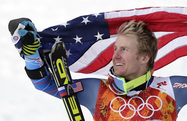 Men's giant slalom gold medalist Ted Ligety of the United States poses for photographers with the American flag on the podium at the Sochi 2014 Winter Olympics, Wednesday, Feb. 19, 2014, in Krasnaya Polyana, Russia.(AP Photo/Charles Krupa)