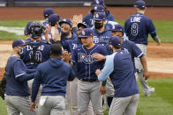 Tampa Bay Rays players congratulate designated hitter Yoshi Tsutsugo, center, who drove in the go-ahead run during the seventh inning of a baseball game against the New York Yankees, Sunday, April 18, 2021, at Yankee Stadium in New York. (AP Photo/Kathy Willens)