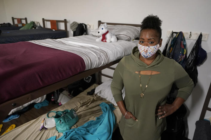 """Cidney Oliver poses for a photo, Wednesday, April 7, 2021, by the bunk she sleeps on at a YWCA shelter for women lacking housing in Seattle. Earlier in the day, Oliver received the first dose of the Moderna COVID-19 vaccine at a clinic staffed by workers from Harborview Medical Center at the shelter. """"It was important for me to protect myself and the health and welfare of others,"""" Oliver said. (AP Photo/Ted S. Warren)"""