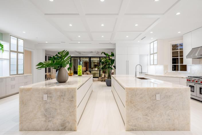 The kitchen features two large oversize central islands covered in white marble.