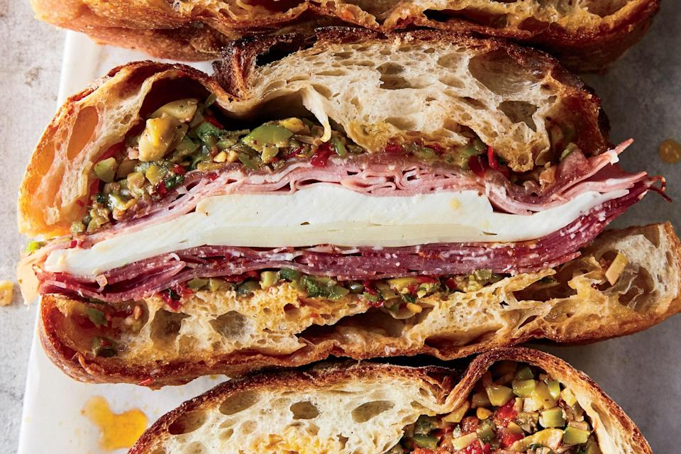 """A big sandwich is guaranteed to light up hungry faces, and this one is truly perfect picnic food. You can't always guarantee sunshine, but you can guarantee smiles from the salty meats and cheeses in this substantial New Orleans classic. <a href=""""https://www.epicurious.com/recipes/food/views/the-ba-muffuletta?mbid=synd_yahoo_rss"""" rel=""""nofollow noopener"""" target=""""_blank"""" data-ylk=""""slk:See recipe."""" class=""""link rapid-noclick-resp"""">See recipe.</a>"""