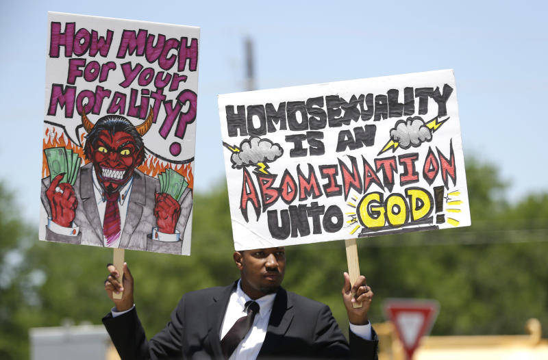 An unidentified protestor holds a sign near where the Boy Scouts of America is holding their annual meeting Wednesday, May 22, 2013, in Grapevine, Texas. Delegates to the meeting are expected to address a proposal to allow gay scouts into the organization. (AP Photo/LM Otero)