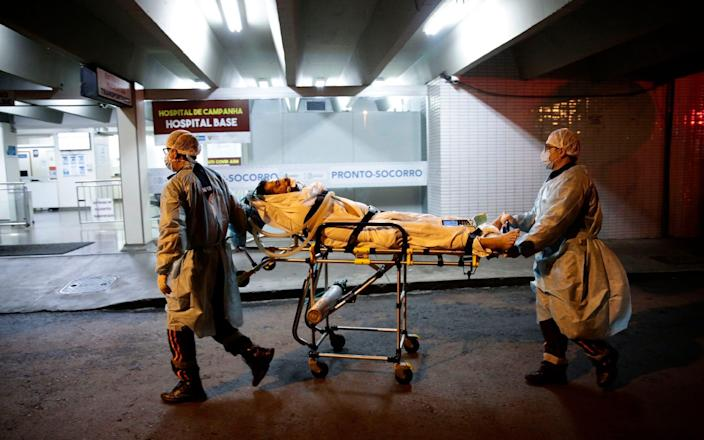Healthcare workers of the public Mobile Emergency Service bring a patient suspected of suffering from Covid-19 to the Base Public Hospital in Brasilia, Brazil - Eraldo Peres/AP