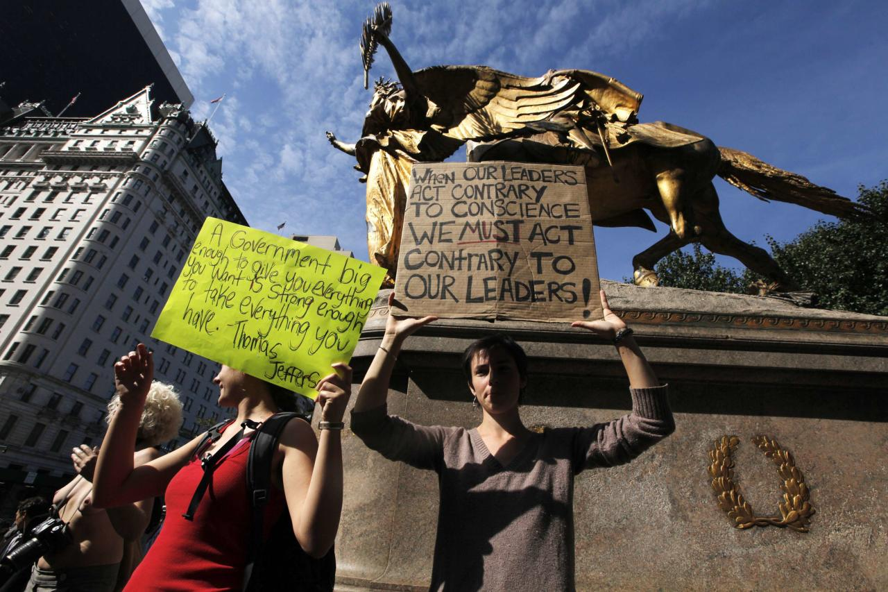 Members of the Occupy Wall St movement hold signs aloft as they protest on 5th Avenue while marching through the upper east side of New York October 11, 2011. Demonstrators taking part in the Occupy Wall St have staged demonstrations protesting income inequality for several weeks while camping in Zuccotti Park.    REUTERS/Lucas Jackson (UNITED STATES - Tags: BUSINESS POLITICS CIVIL UNREST)