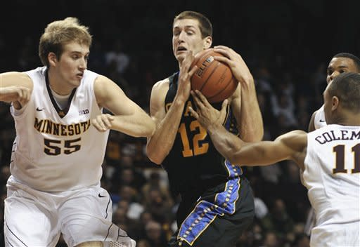 South Dakota State's Brayden Carlson, center, attempts to drive past Minnesota's Elliot Eliason, left, and Joe Coleman during the first half of an NCAA college basketball game, Tuesday, Dec. 4, 2012, in Minneapolis. (AP Photo/Tom Olmscheid)