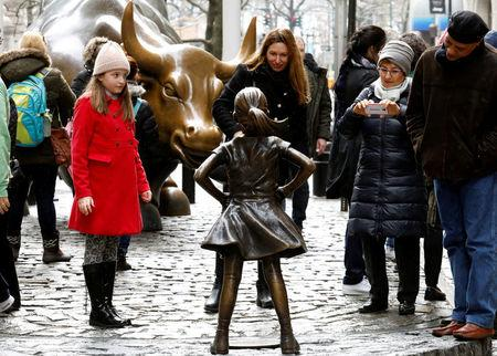 People look at a statue of a girl facing the Wall St. Bull, as part of a campaign by U.S. fund manager State Street to push companies to put women on their boards, in the financial district in New York, U.S., March 7, 2017. REUTERS/Brendan McDermid