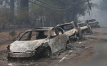 FILE - In this Nov. 9, 2018, file photo, the burned out hulks of cars abandoned by their drivers sit along a road in Paradise, Calif. A lack of escape routes out of Paradise caused many people fleeing the fire to abandon their vehicles and run for their lives. (AP Photo/Rich Pedroncelli, File)