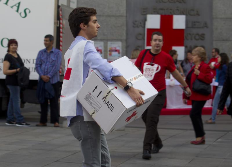 A Red Cross worker carries a box in Madrid, Wednesday Oct. 10, 2012. Spain's Red Cross is launching its first-ever public appeal for donations to help the growing number of Spaniards in need of help because of the economic crisis. Spokesman Miguel Angel Rodriguez said Tuesday the agency is looking to round up some euro 30 million ($38.87 million) over the next two years to help an extra 300,000 people. (AP Photo/Paul White)