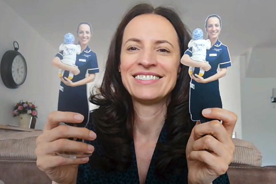 In this image taken from an online video interview with The Associated Press, Claudia Anghel, a Romanian midwife working in England, poses with two cardboard representations of herself, received from a patient as a thank you present, in Nuneaton, England, Tuesday, July, 28, 2020. Anghel's success story as one of 600,000 Romanians in Britain is at the same time a telling sign of how the deficiencies of her home country's health care system and the bleak prospects for a better future for herself and her family have left huge gaps in Romanian society and its health care system. (AP Photo)