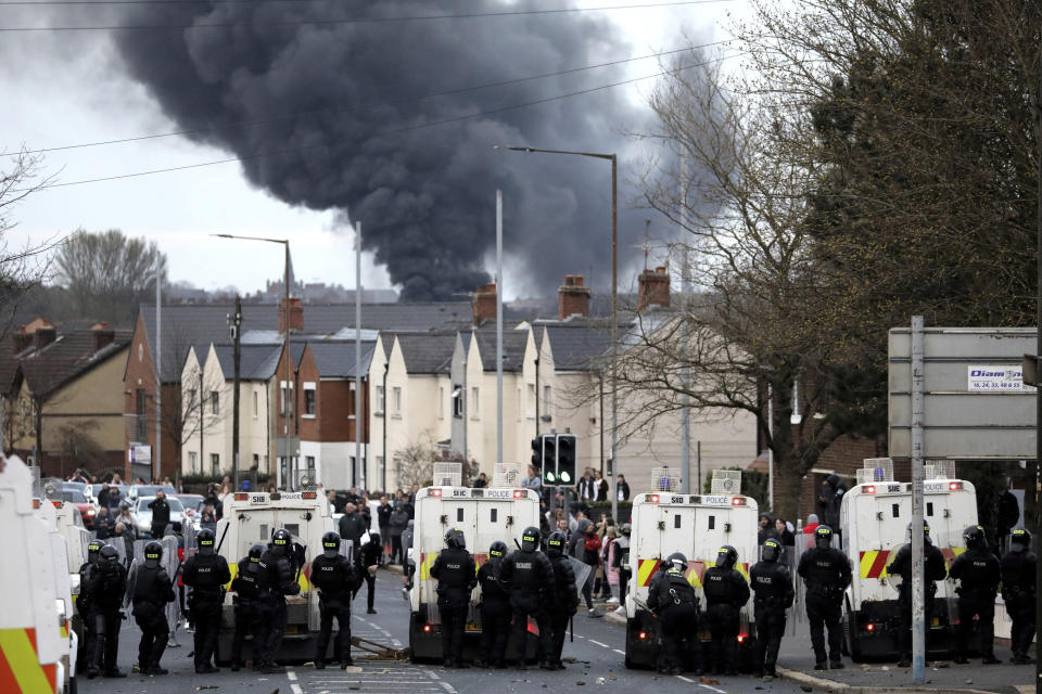 """FILE - In this Wednesday, April 7, 2021 file photo, police form a line on the Springfield road to stop Nationalists and Loyalists attacking each other, as a hijacked bus burns in the distance in Belfast, Northern Ireland. The chaotic scenes during a week of violence on the streets of Northern Ireland have stirred memories of decades of Catholic-Protestant conflict, known as """"The Troubles."""" A 1998 peace deal ended large-scale violence but did not resolve Northern Ireland's deep-rooted tensions. (AP Photo/Peter Morrison, File)"""