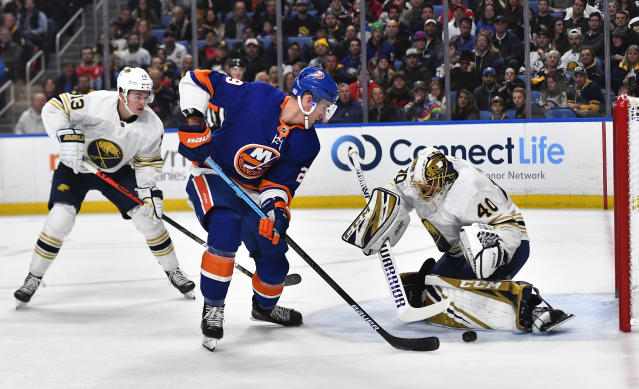 Buffalo Sabres goalie Carter Hutton, right, makes a save against New York Islanders center Brock Nelson, center, as Sabres left wing Jimmy Vesey trails the play during the first period of an NHL hockey game in Buffalo, N.Y., Saturday, Nov. 2, 2019. (AP Photo/Adrian Kraus)