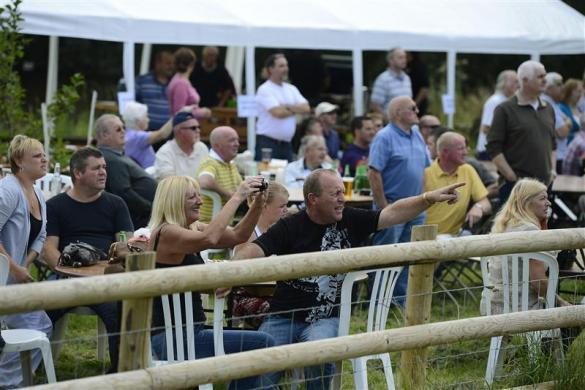 Pigeon owners react as the first pigeons arrive back during the One Loft race at Birtsmorton, central England August 26, 2012.