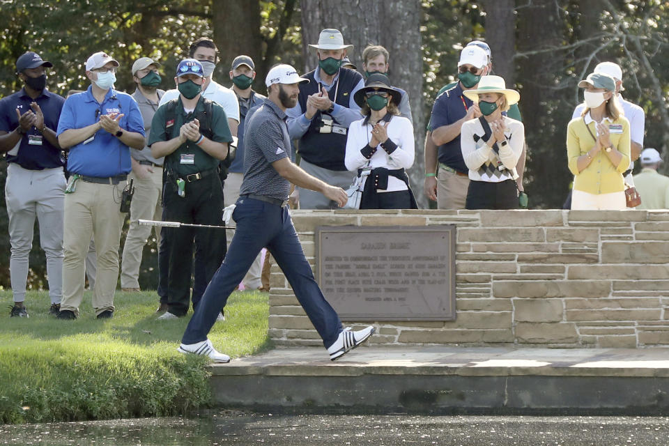 Dustin Johnson walks over the Sarazen Bridge on his way to the 15th green as spectators applaud during the final round of the Masters golf tournament Sunday, Nov. 15, 2020, in Augusta, Ga. (Curtis Compton/Atlanta Journal-Constitution via AP)