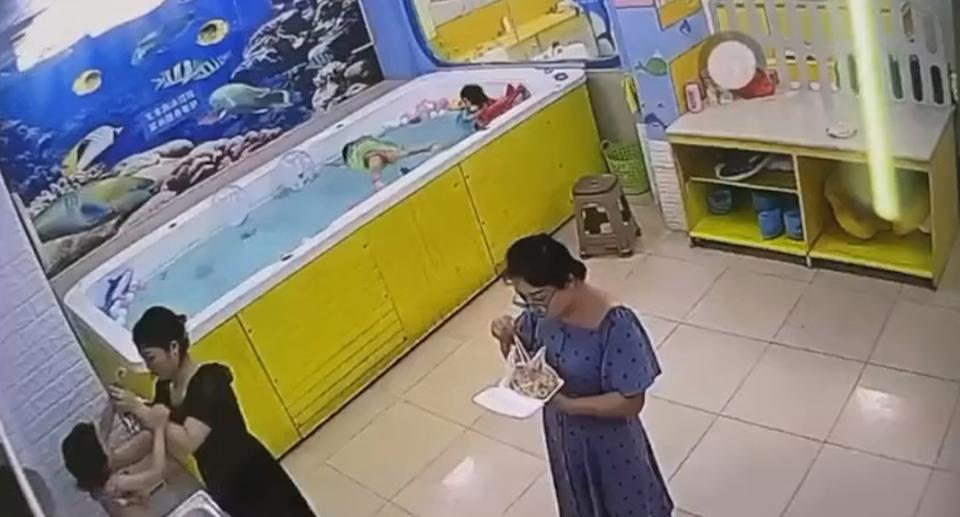 A woman eating and another changing the clothes of a child fail to notice the drowning tragedy of a little girl in China.