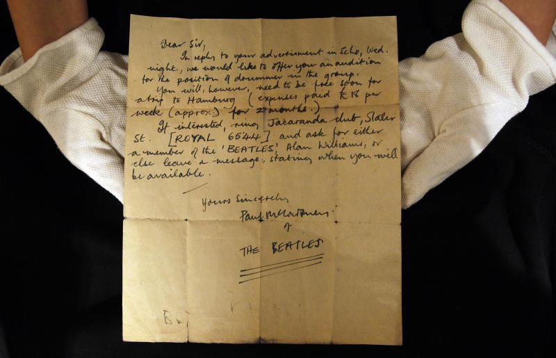A Christie's employee displays a letter  inviting an unknown drummer to audition for The Beatles, at their auction house in London,  Monday, Oct. 17, 2011. The handwritten letter by Paul McCartney, dated 12 August 1960, inviting an unknown drummer to audition for The Beatles, was discovered folded-up inside a book, by an anonymous collector at a car boot sale in Bootle, Liverpool, England. It is expected to sell at auction for 7,000-9,000 pounds (11,050- 14,200 US dollars). (AP Photo/Kirsty Wigglesworth)