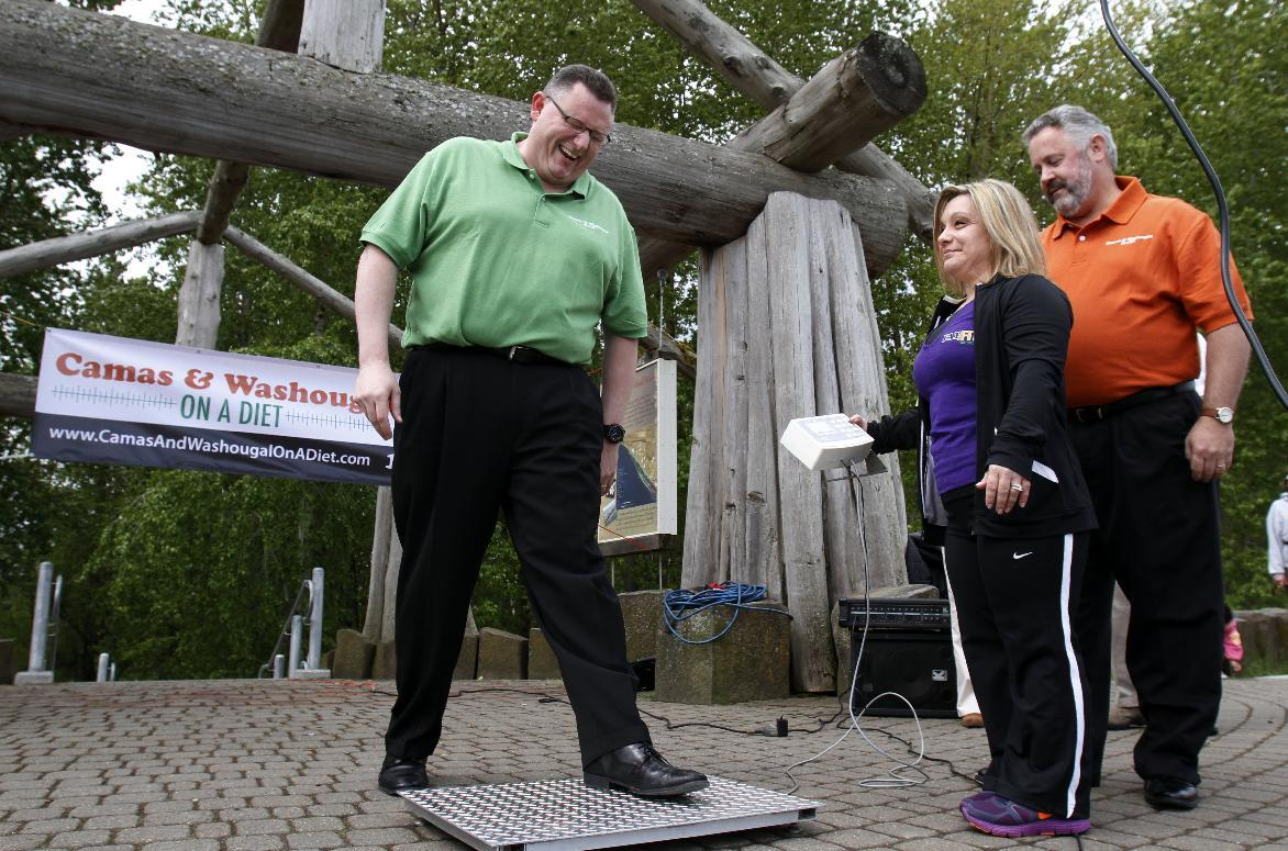 "Camas Mayor Scott Higgins, left, steps on the scales as Washougal Mayor Sean Guard, right, and health coach Michelle Clark watch during their weigh-in in Washougal, Wash., Wednesday, May 2, 2012. The mayors of the two neighboring Washington state towns on the banks of the Columbia River are embarking on a ""Biggest Loser"" style contest to see which of the two communities can lose the most weight in 12 months. (AP Photo/Don Ryan)"