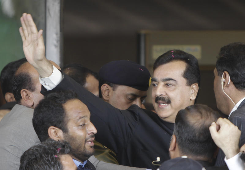 Pakistani Prime Minister Yousuf Raza Gilani, center, waves upon his arrival at the Supreme Court for a hearing in Islamabad, Pakistan, Thursday, April 26, 2012. The Supreme Court convicted Gilani of contempt on Thursday for refusing to reopen an old corruption case against President Asif Ali Zardari on Thursday, but spared him a prison term in a case that has stoked political tensions in the country. (AP Photo/B.K. Bangash)