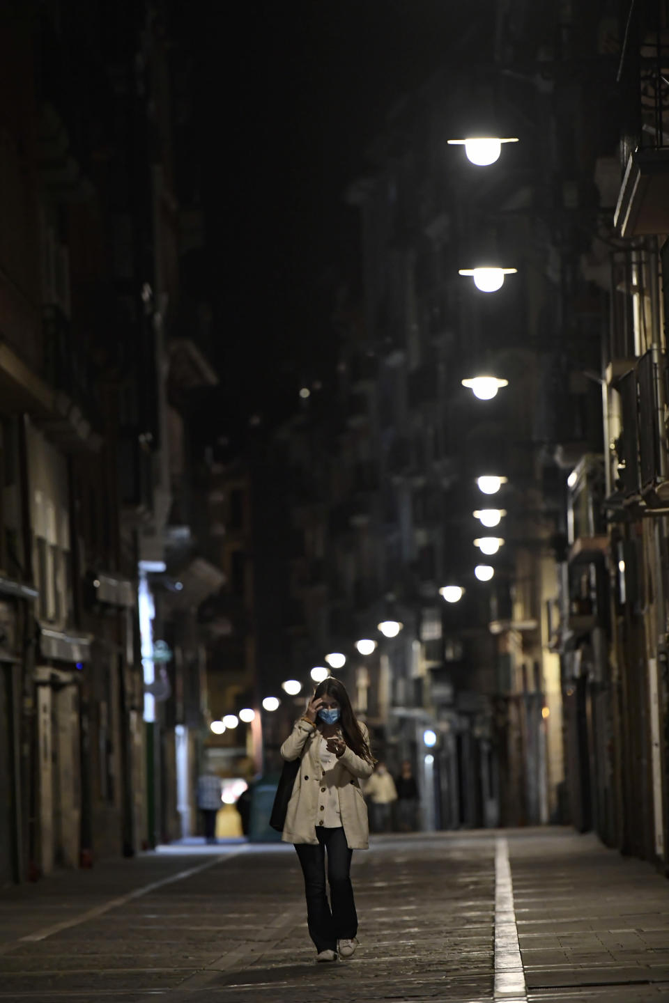 A resident wearing face mask protection walks along an empty Estafeta street, in Pamplona, northern Spain, Saturday, Oct. 24, 2020, as new measures against the coronavirus began in the Navarra province where all bar and restaurants are closing for 15 days. (AP Photo/Alvaro Barrientos)