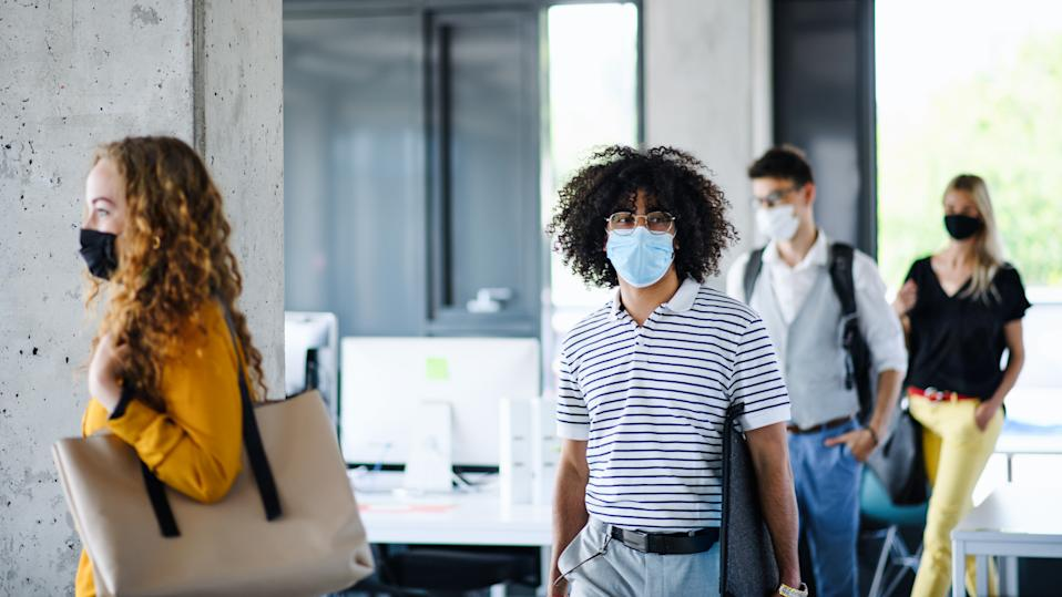 Young people with face masks back at work in office after coronavirus quarantine and lockdown, walking.