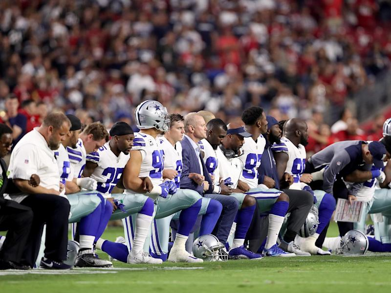 Members of the Dallas Cowboys link arms before the start of their NFL game against the Arizona Cardinals: Getty