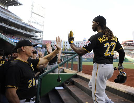 Pittsburgh Pirates' Andrew McCutchen (22) celebrates his two-rum home with bench coach Jeff Banister (28) and other teammates in the dugout against the Washington Nationals during the first inning of a baseball game, Monday, July 22, 2013, in Washington. (AP Photo/Nick Wass)