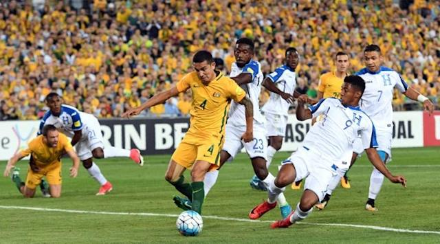 Australia's Tim Cahill (C) shoots on goal as he is tackled by Honduras' players during their FIFA 2018 World Cup qualification play-off 2nd leg match, in Sydney, on November 15, 2017