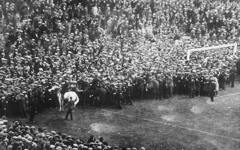 Police clear fans off of the pitch during the famous White Horse FA Cup Final between Bolton and West Ham at Wembley Stadium - Credit: Allsport Hulton Getty/ALLSPORT