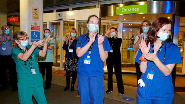 PHOTO: Members of staff at the Chelsea and Westminster Hospital take part in the Clap for Captain Tom Moore on Feb. 3, 2021 following his death and NHS staff. (Niklas Halle'n/AFP via Getty Images)