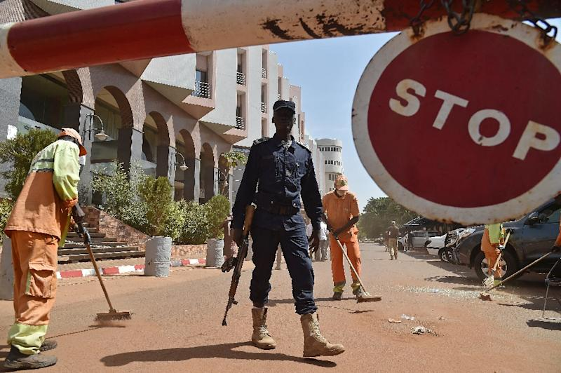 A Malian police officer stands guard as workers clean up ouside the Radisson Blu hotel in Bamako on November 22, 2015, two days after a deadly attack (AFP Photo/Issouf Sanogo)