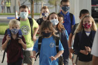 Students arrive to on the firs day to the newly-rebuilt Addison Mizner School in Boca Raton, Tuesday, Aug. 10, 2021. Palm Beach County Schools opened the school year with a masking requirement with an opt-out option. (Joe Cavaretta/South Florida Sun-Sentinel via AP)