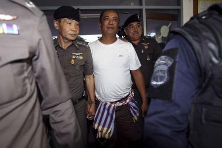 Patchuban Angchotipan (C), a suspected kingpin of a human trafficking network, is escorted by policemen at Hat Yai police station May 18, 2015. Picture taken May 18, 2015.   REUTERS/Stringer