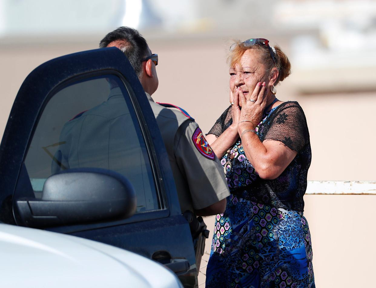 Shooting survivor Virginia Chacon talks with Texas Highway Patrol trooper Gilbert Flores outside the Walmart in El Paso on Aug. 3, 2019. Chacon was inside the store when gunfire broke out and escape by running.