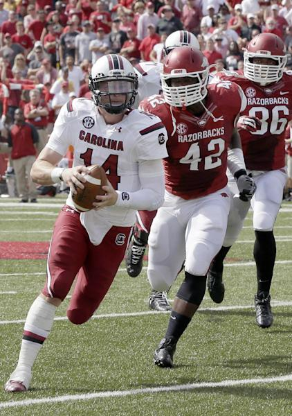 South Carolina quarterback Connor Shaw (14) carries in front of Arkansas defensive end Chris Smith (42) and defensive end Trey Flowers (86) during the second quarter of an NCAA college football game in Fayetteville, Ark., Saturday, Oct. 12, 2013. (AP Photo/Danny Johnston)