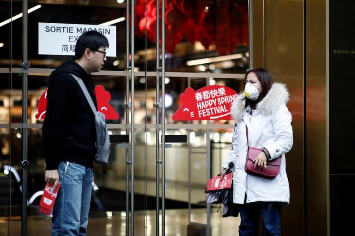 Tourist wears a protective mask as she leaves the Galeries Lafayette department store in Paris as the country is hit by the new coronavirus