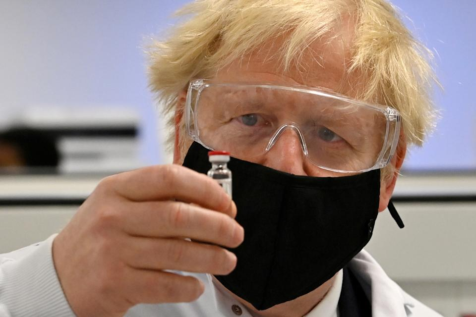 Britain's prime minister Boris Johnson inspects a vial of the AstraZeneca/Oxford University COVID-19 candidate vaccine. Photo: Paul Ellis/Pool via Reuters