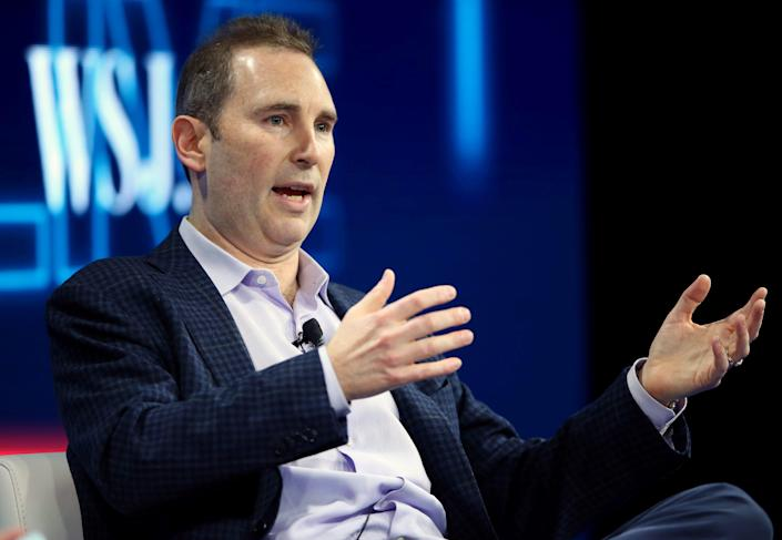 Amazon CEO Andy Jassy motions with his hands on stage at a conference.