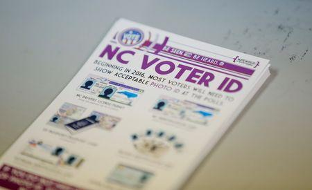 """A pile of government pamphlets explaining North Carolina's controversial """"Voter ID"""" law sits on table at a polling station as the law goes into effect for the state's presidential primary in Charlotte, North Carolina, U.S. on March 15, 2016. REUTERS/Chris Keane/File Photo"""
