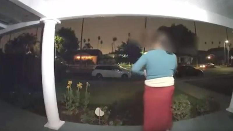 A still from a video where a potential kidnapping is heard being carried out and was captured on a Los Angeles doorbell camera. A woman, who is appears to be a witness, stands on her front porch as the incident unfolds.