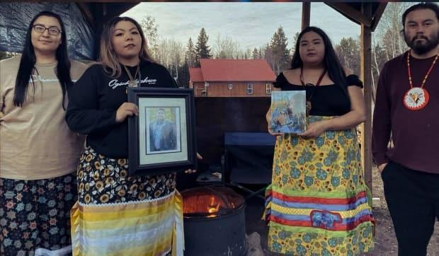 Cheynna Gardner, second from left, surrounded by friends, lit a sacred fire in her home First Nation of Migisi Sahgaigan to shine a spotlight on the issue of sexual violence. They hold the photos of two loved ones who died in 2020. (Submitted by Cheynna Gardner - image credit)
