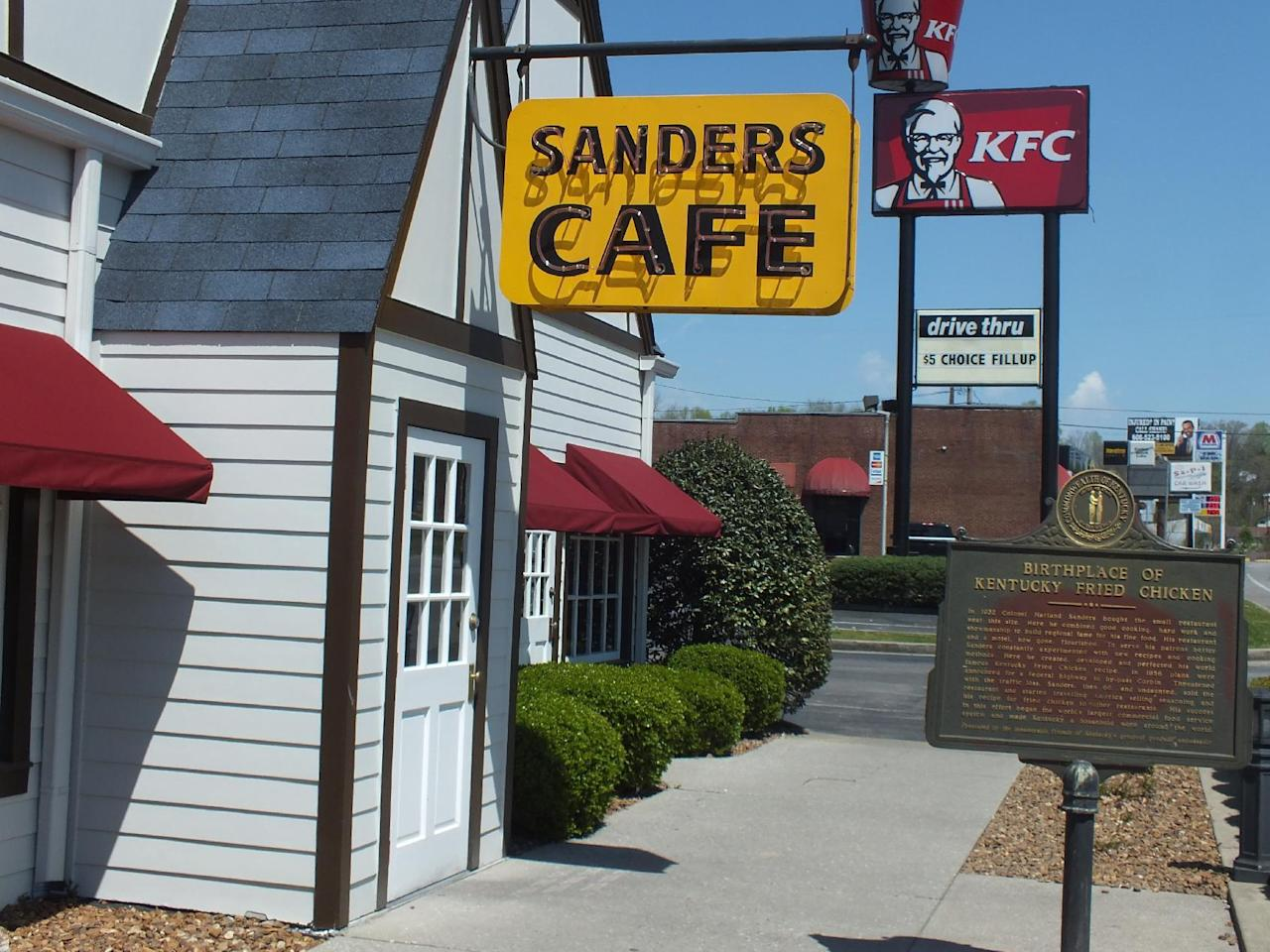This August 2016 photo, show, the original Sanders Cafe sign, dwarfed by a newer KFC sign and bucket, that tower over the Corbin, Ky., restaurant. KFC says the recipe published in the Chicago Tribune is not authentic. But that hasn't stopped rampant online speculation that one of the most legendary and closely guarded secrets in the history of fast food has been exposed. (Jay Jones/Chicago Tribune via AP)