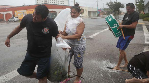 PHOTO: People clear debris out of a drainage ditch in an attempt to keep the area from flooding as Hurricane Irma passes through on Sept. 10, 2017 in Miami. (Joe Raedle/Getty Images)