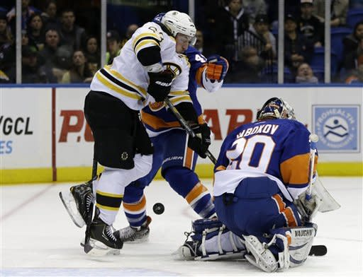 New York Islanders defenseman Andrew MacDonald (47) and goalie Evgeni Nabokov (20) cannot block a shot by Boston Bruins defenseman Adam McQuaid, not shown, as left wing Brad Marchand (63) jumps out of the way in the first period of their NHL hockey game at Nassau Coliseum in Uniondale, N.Y., Tuesday, Feb. 26, 2013. McQuaid scored on the shot. (AP Photo/Kathy Willens)