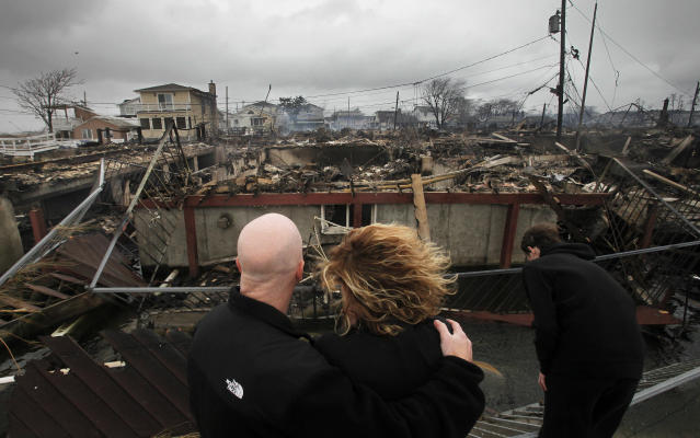 Robert Connolly, left, embraces his wife, Laura, as they survey the remains of the home owned by her parents, in the Breezy Point section of New York, October 2012. (Photo: Mark Lennihan/AP)