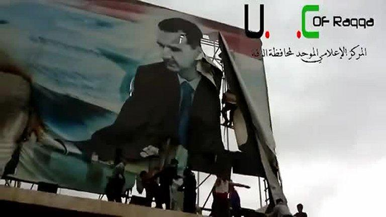 An image from a video on YouTube shows Syrian protesters tearing a billboard of President Assad in Raqqa, March 4, 2013