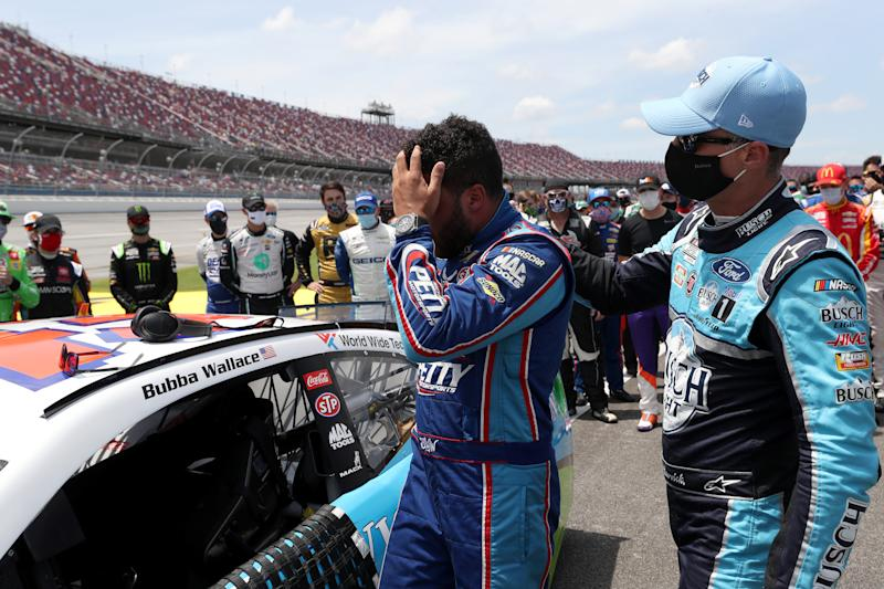 TALLADEGA, ALABAMA - JUNE 22: Bubba Wallace, driver of the #43 Victory Junction Chevrolet, is greeted by Kevin Harvick, driver of the #4 Busch Light Ford, after NASCAR drivers pushed Wallace to the front of the grid as a sign of solidarity with the driver prior to the NASCAR Cup Series GEICO 500 at Talladega Superspeedway on June 22, 2020 in Talladega, Alabama. A noose was found in the garage stall of NASCAR driver Bubba Wallace at Talladega Superspeedway a week after the organization banned the Confederate flag at its facilities. (Photo by Chris Graythen/Getty Images)