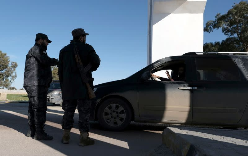 Policemen stand near a gate at the western entrance to the city of Benghazi