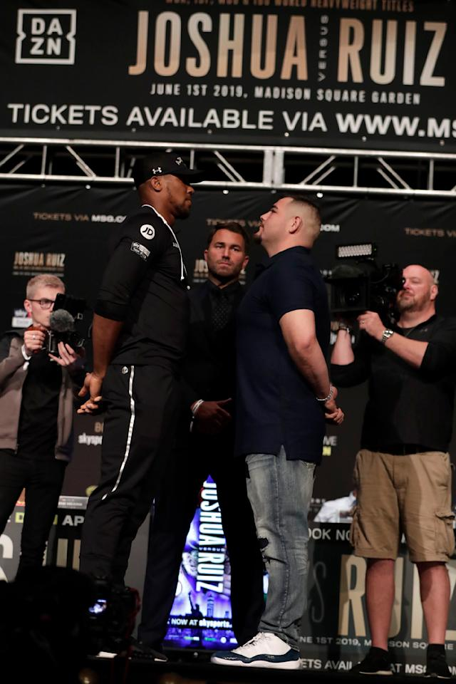 CORRECTS NAME TO ANDY RUIZ NOT ANDY GREEN AS ORIGINALLY SENT - British boxer Anthony Joshua, left, faces off against Andy Ruiz before a press conference ahead of their heavyweight bout, Thursday, May 30, 2019, in New York. Joshua will defend his WBA, WBO and IBF heavyweight titles. (AP Photo/Julio Cortez)