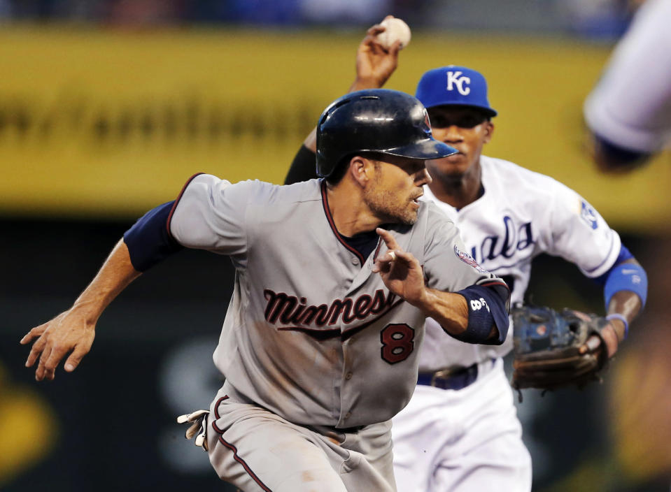 Minnesota Twins' Jamey Carroll (8) gets caught in a rundown with Kansas City Royals shortstop Alcides Escobar, back, during the fifth inning of a baseball game at Kauffman Stadium in Kansas City, Mo., Tuesday, Aug. 6, 2013. Carroll was tagged out by Royals third baseman Mike Moustakas on the play. (AP Photo/Orlin Wagner)
