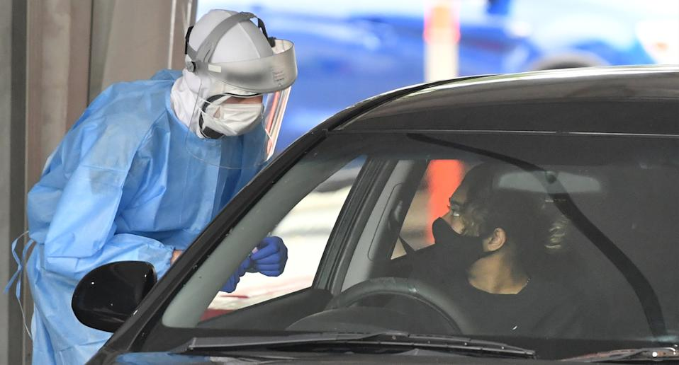 A health care worker (left) is seen testing people at a COVID-19 drive through testing clinic at Murarrie in Brisbane