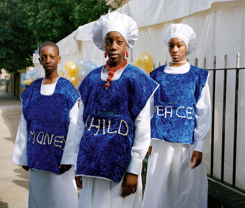 Josiah, Bukky and Lauren stand outside church on children's anniversary service wearing clothing that reads Money, Child, Peace as they collect donations from their fellow congregants for charity. | Sophie Green